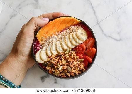 Smoothie Bowl With Strawberry, Dragon Fruit, Mango And Granola In Coconut N Bowl On White Table, Top