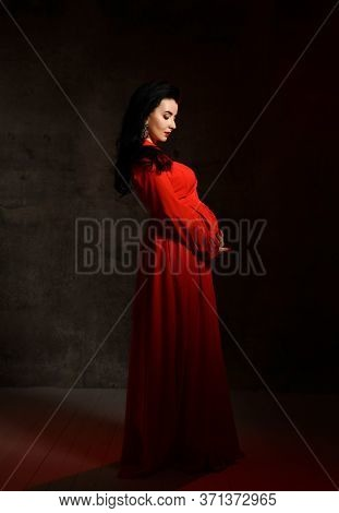 Portrait Of Young Beautiful Pregnant Woman In Red Elegant Maxi Dress Standing, Embracing Belly And L