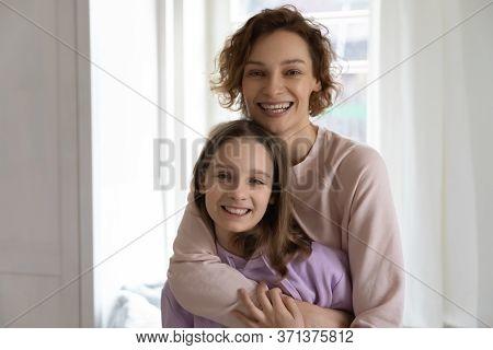 Portrait Of Happy Mom And Teen Daughter Hugging