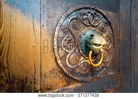 Detail Of Old Wooden Door With Metal Handle On Board With Carved Pattern. Dark Brown Solid Front Doo