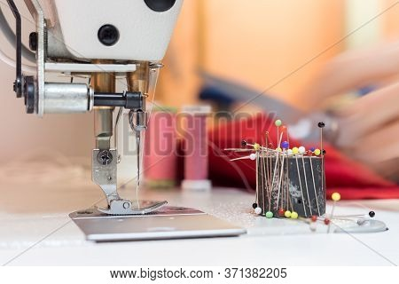 Sewing Machine And Needle In A Dressmaker Workshop: Close Up Tailor Hands Holding A Needle