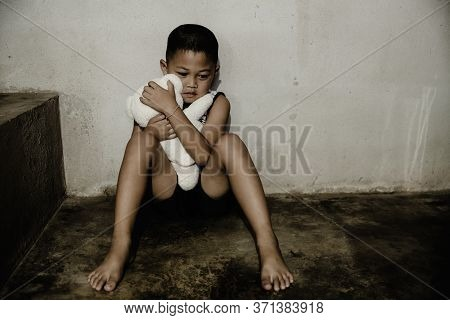 Neglected Lonely Child, Young Boy Sitting With A Doll On The Floor With Copy Space.