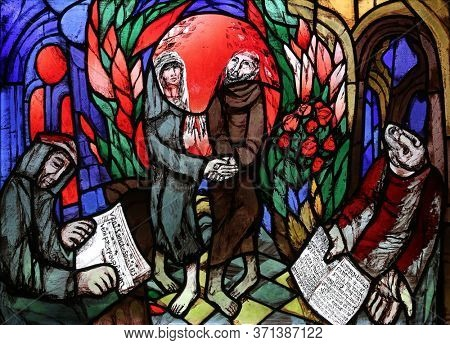 ELLWANGEN, GERMANY - MAY 05, 2014: St. Francis of Assisi dances with a woman of poverty in the joy of the Holy Spirit, stained glass window at Holy Spirit church in Ellwangen, Germany
