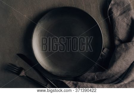 Black Table Setting: Plate, Napkin, Silverware On Black Wooden Background. Top View. Flat Lay.