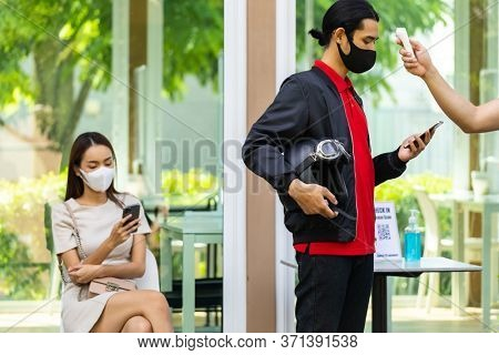 Take Temperature for customer with face mask before getting in restaurant with social distance queue in line new normal after coronavirus covid-19 pandemic. Restaurant New normal concept.