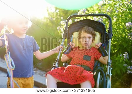 Communication Of Boy And A Disabled Girl In A Wheelchair Walking In The Park Summer. Inclusion. Chil