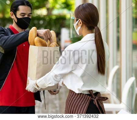 Deliverly asian bike man pick up bakery grocery bag from bakery shop to deliver to customer who make online order. Food deliverly service concept in new normal after coronavirus pandemic.