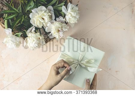 Woman Opening Her Present, Top View. Female's Hands Pull Ribbon To Unwrap Gift Box Among The White P
