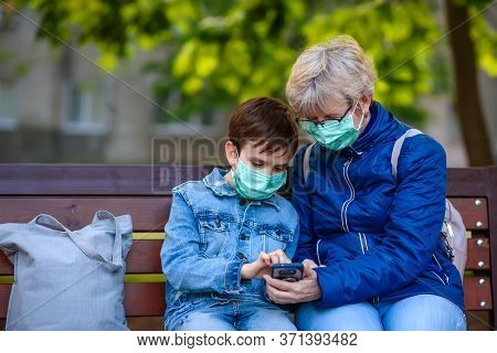 Grandmother With Grandson In Medical Masks Sit In Park With A Smartphone. Boy Shows To Grandmother O