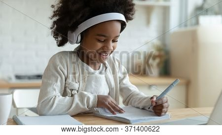 African Schoolgirl Sit At Table Writing In Workbook Studying Distantly