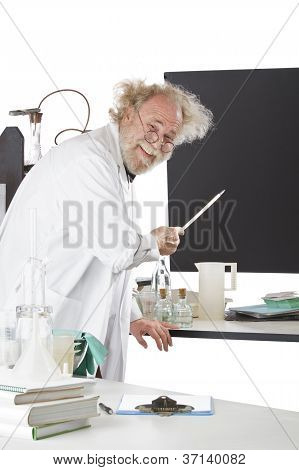 Smiling Eccentric  Scientist Points To Blackboard