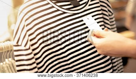 Closeup Woman's Hand Choosing The Clothes Hanking On The Rack In The Store. The Clothes During Shopp