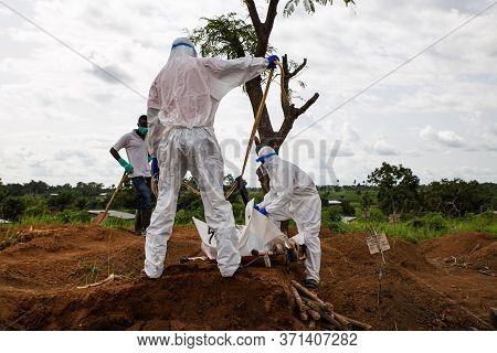 Lunsar, Sierra Leone - June 24, 2015: Members Of The Burial Team Bury An Ebola Dead Person In The Ma