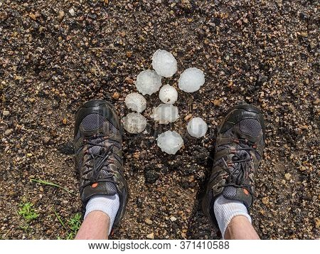 Golf Ball And Tennis Ball Sized Hail On The Ground With Person's Feet.