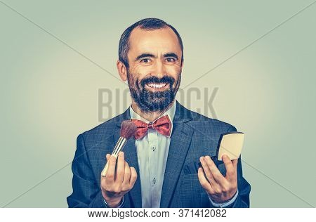Funny Bearded Business Man Holding Brush And Makeup Compact Loose Powder Looking At You Camera. Mixe