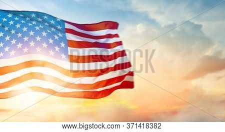 Patriotic holiday. The USA are celebrating 4th of July. American flag on sunset background.