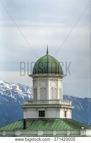 Building Exterior With Green Dome And Roof Against Snowy Mountain And Cloudy Sky