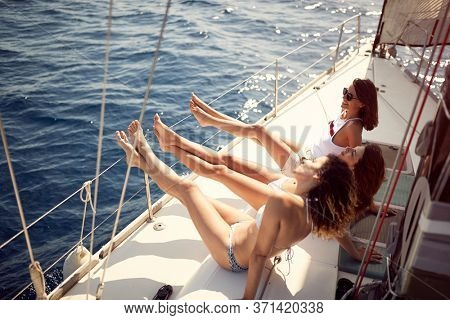 Happy girls sailing on yacht. Vacation, travel, sea, friendship and people concept.