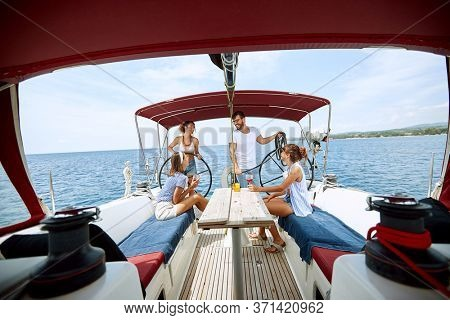 Happy friends  drinking on a yacht.Smiling  friends on vacation and luxury travel.