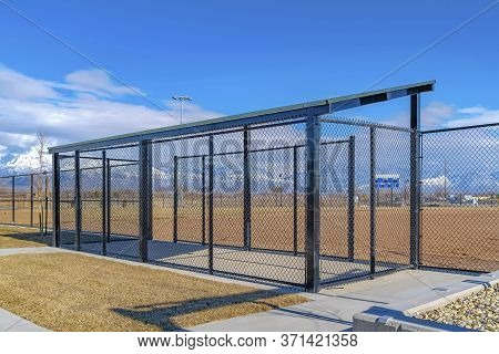 Baseball Field Dugout With Slanted Roof And Chain Link Fence On A Sunny Day