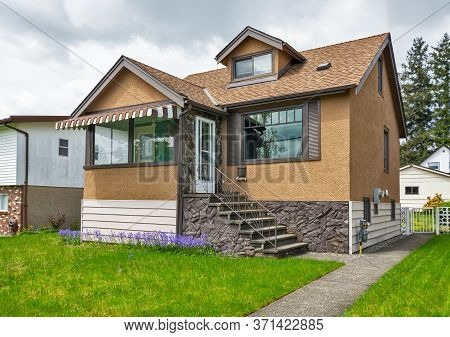 Modest Family House With Green Lawn In Front. Old Residential House