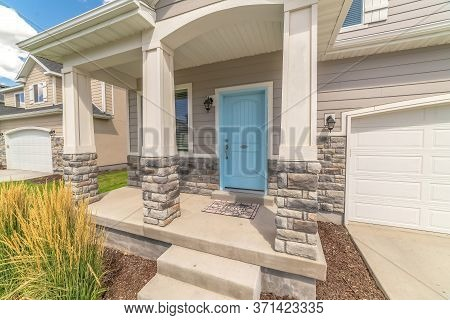 Stape And Arched Entrance At The Porch Of Home With Pastel Blue Front Door