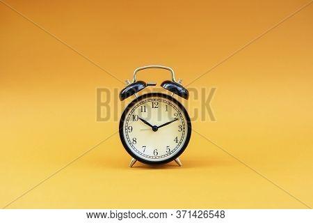 Black Retro Alarm Clock Is Centered On An Orange Background.