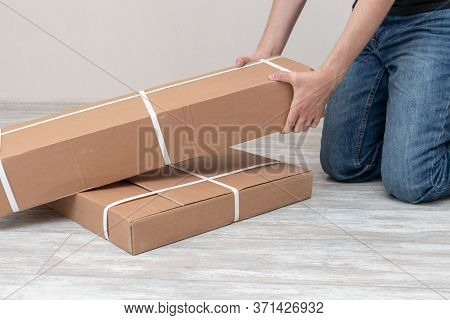 Man Assembling Of Furniture In Packed Boxes. Furniture Assembly Parts.