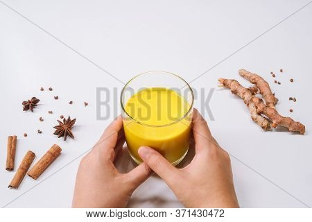 Hands Holding Glass Of Golden Milk Turmeric Curcumin Latte Yellow Drink On White Table Background Wi