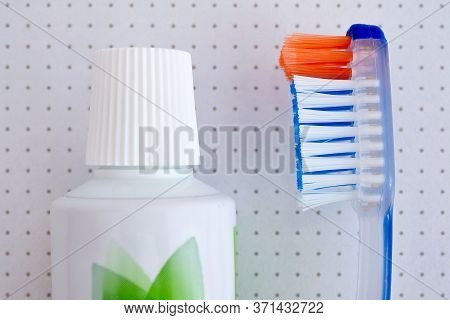 A Toothbrush And A Tube Of Toothpaste Lie In Close-up On The White Speckled Surface Of A Washing Mac