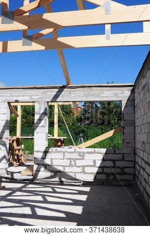 Building A New House Construction With Brick Walls, Large Window And Doorway Frame With The View Fro