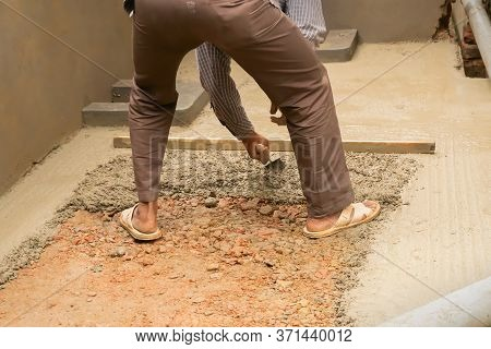 Indian Construction Worker Plastering Floor Using Trowel And Cement Manually, Stock Image.