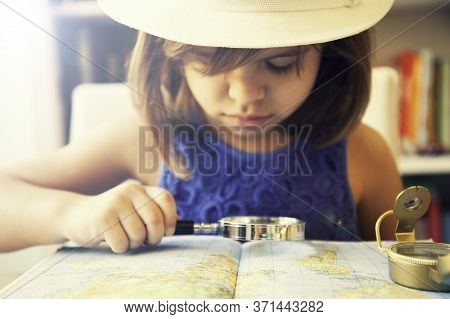 Trendy Little Girl In Summer Casual Wear And White Hat, Looking The World Map With Magnifying Glass