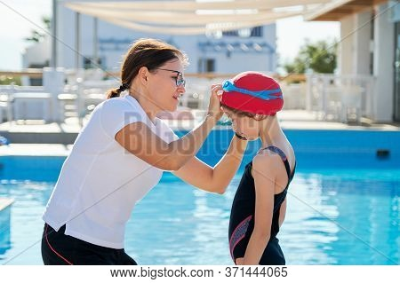 Family, Sport, Swimming, Health, Lifestyle Concept. Mom Helps Daughter Child Wear Swimming Goggles,