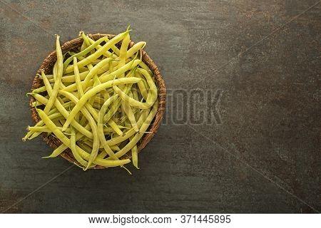 Fresh Picked Yellow Wax Beans In To Basket On Dark Background