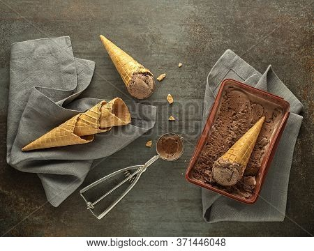Chocolate Ice Cream Scoops, Scooped Out Of Container In To Waffle Cones With A Silver Utensil