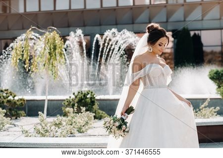 Portrait Of The Bride In The City Near The Fountain.a Stunning Young Bride With Curly Hair . Wedding