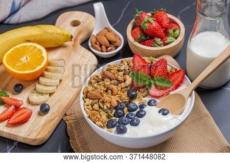 Bowl Of Homemade Granola Yogurt With Fresh Berries On Breakfast Table Milk And Mixed Fruit.