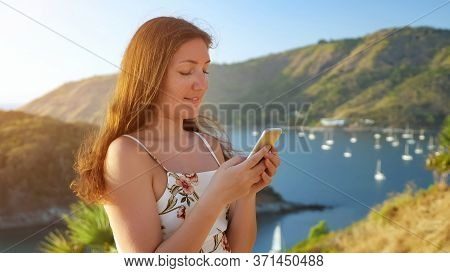 Brunette With Long Loose Hair Waved By Wind Types On Modern Smartphone Standing In Hilltop Against B