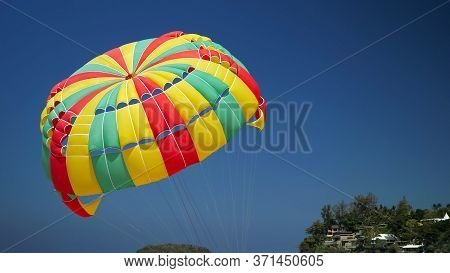 Wonderful Red Green Yellow Parachute Moves Under Clear Blue Sky Against Green Hilltop With Small Bui