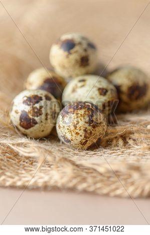Quail Eggs On A Burlap Cloth. Rustic Still Life With Quail Eggs. Small Colorful Quail Eggs Close-up.