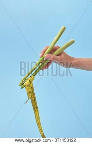 Asparagus spears in a woman's hand holding yellow measuring tape as a noodle against pastel blue background, copy space. Yellow measuring tape as Japanese or Chinese food.