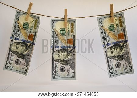 100 Dollars On A Rope, Dollars With A Clothespin On A Rope Isolated On A White Background, Concept -