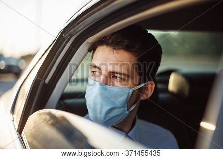 Young Businessman Takes A Taxi And Looks Out Of The Car Window Wearing Sterile Medical Mask. A Man S
