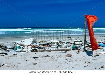 Plastic Bottles And Other Rubbish Thrown On The Sandy Seashore, Trash On The Sea Beach. Ecological P