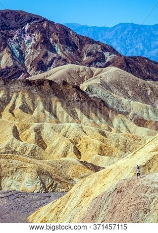 Zabriskie Point. USA. Magnificent landscape in multicolor sunset. Desert at the dry lake bottom - Death Valley in California. The concept of active, extreme and photo tourism