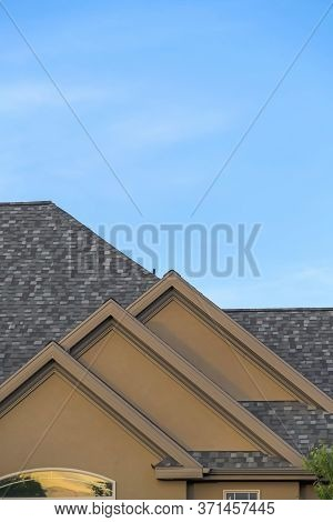 Home Exterior With Front Gable Roof And Transom Window Against Blue Sky