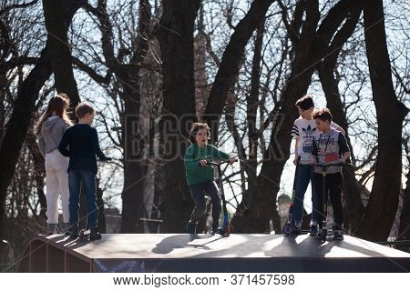 Lviv, Ukraine - March 12, 2020: Kids Ride On Scooter At Skate Park. Child Has Fun With Scooter
