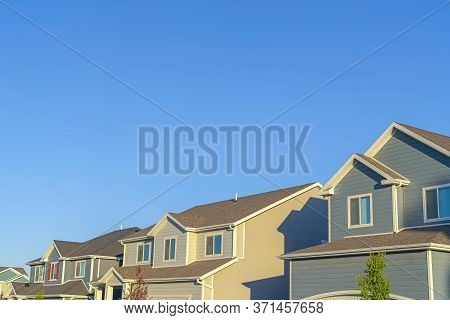 Homes With Horizontal Wall Sidings And Front Gable Roofs Againts Clear Blue Sky