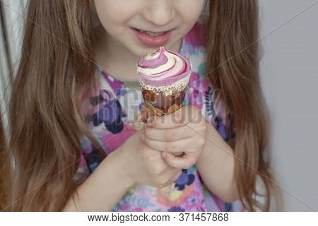 Seven Year Old Girl Eats Ice Cream. She Holds It In Her Hands. Dessert With Raspberry Flavor. Close-